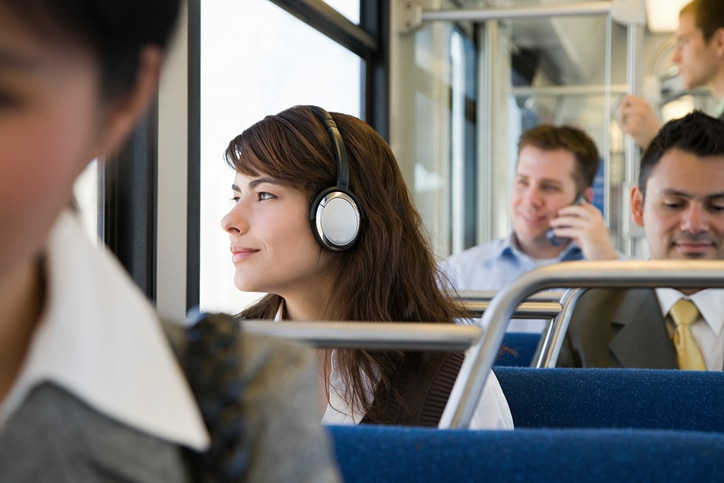 Girl with headphones sitting on the train