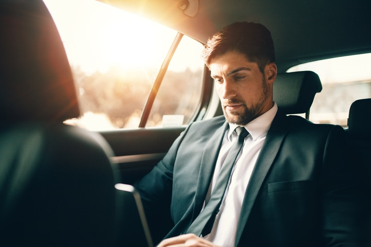 Business man working on laptop in car
