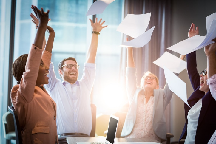 Group of office workers throwing paper into the air