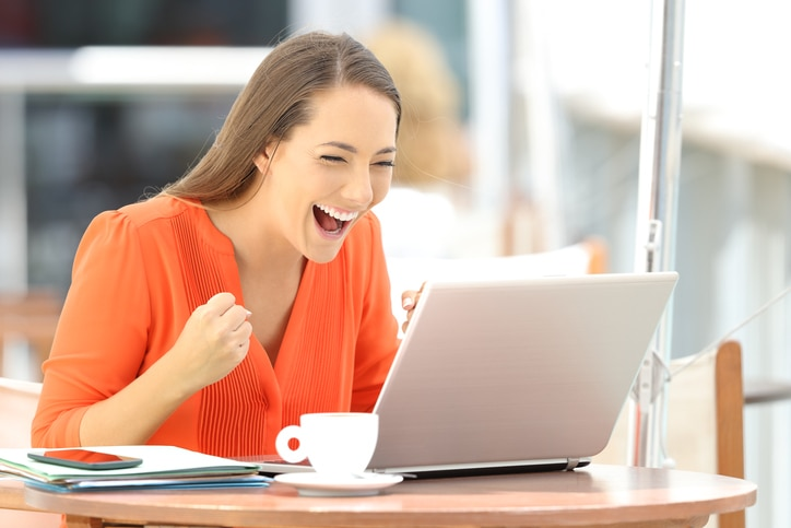 Girl receiving excited news at laptop