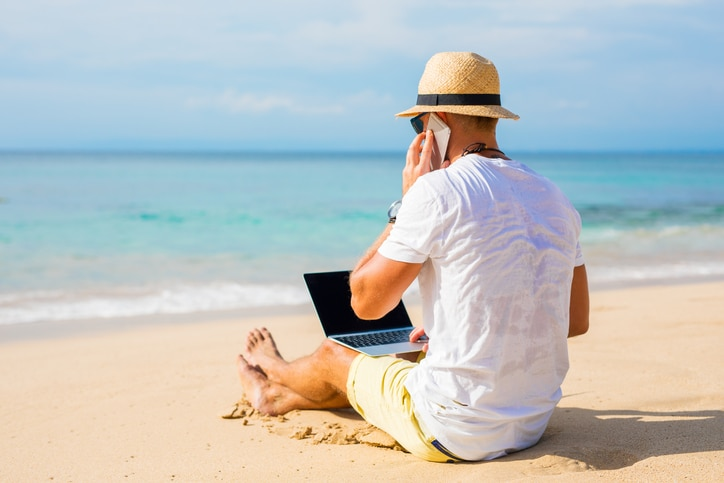 Man sitting on beach holding laptop and phone