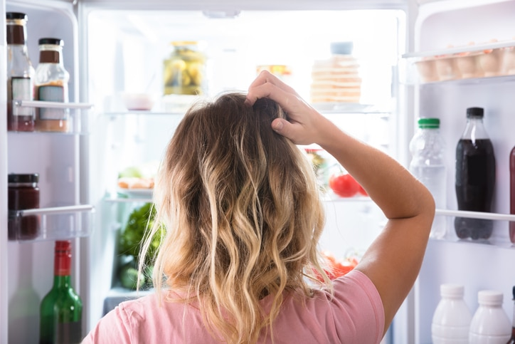 Girl standing at fridge