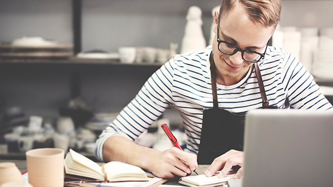 Small business owner writing on a notepad in front of a laptop