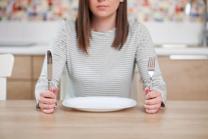 Girl with empty plate holding knife and fork