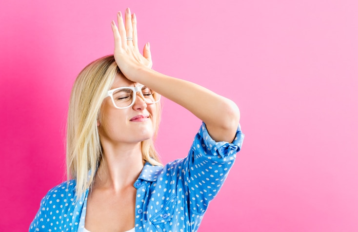 Woman banging palm of hand on forehead