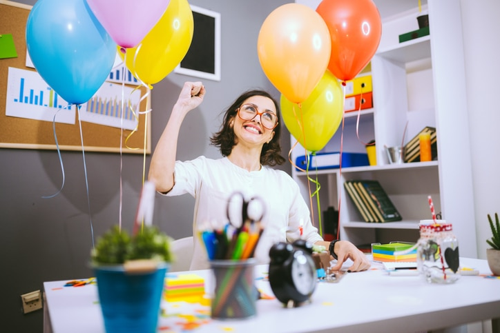 Girl at desk surrounded by balloons