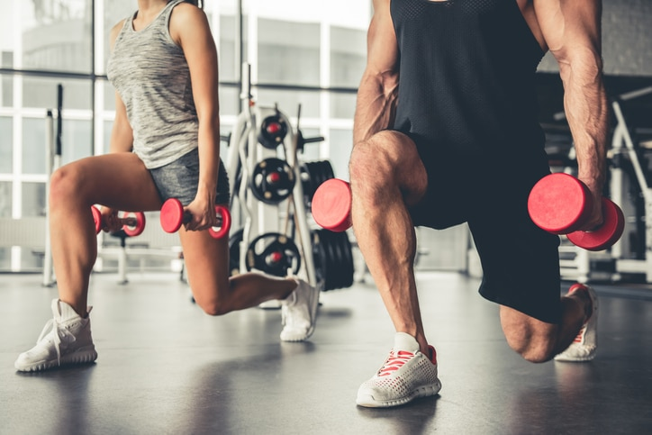 Man and woman doing lunges at a gym