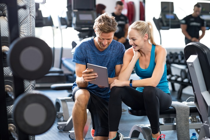 Two people looking at an ipad in a gym