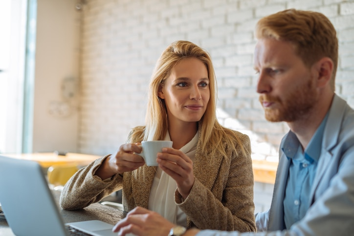 Man and woman having coffee with laptop