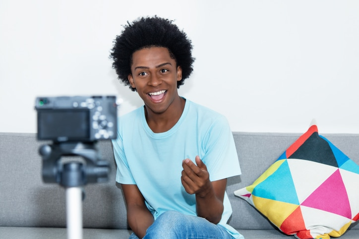 Man on couch filming a video