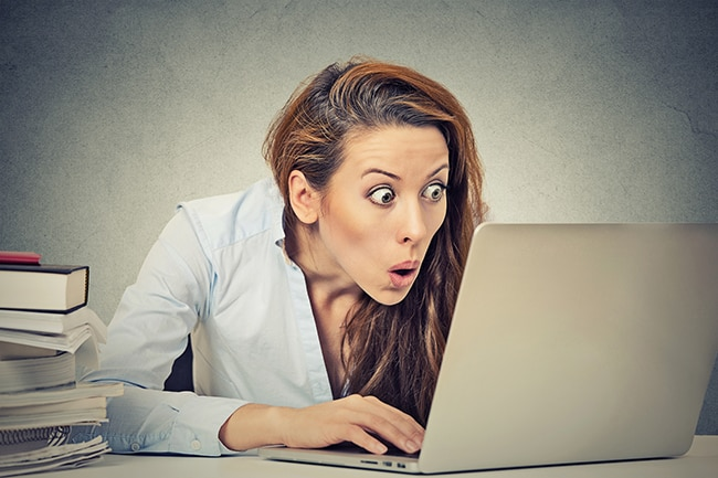 Portrait young shocked business woman sitting in front of laptop computer looking at screen isolated on grey wall background. Funny face expression emotion feelings problem perception reaction