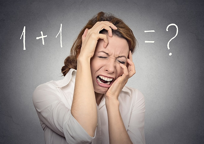 stressed woman can't solve math financial problem isolated on grey wall background. Human face expressions, emotions, feelings