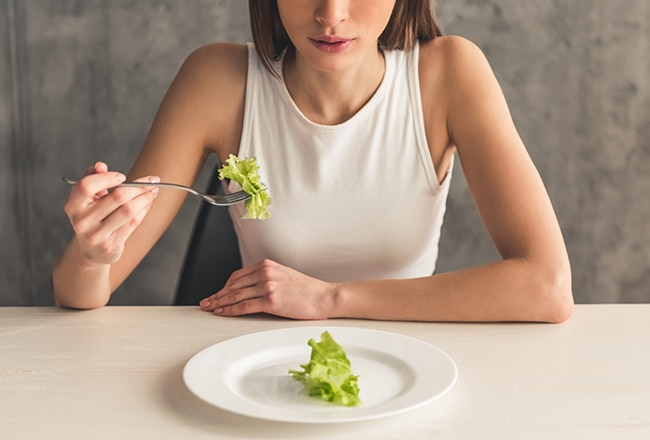 Girl eating a piece of lettuce