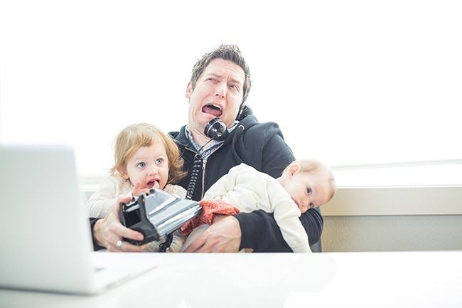 A dad tries to multitask in the office with work and parenting and finds it frustrating. The dad is sitting in his office holding two young daughters and talking on the phone with his laptop open on his desk.