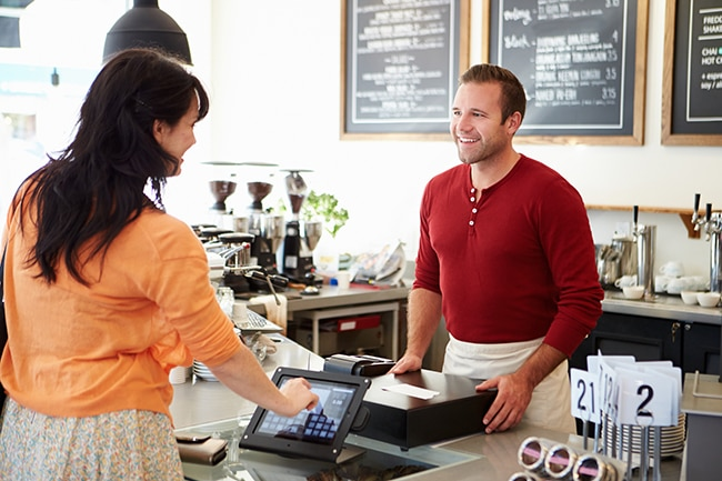 Man serving woman in coffee shop