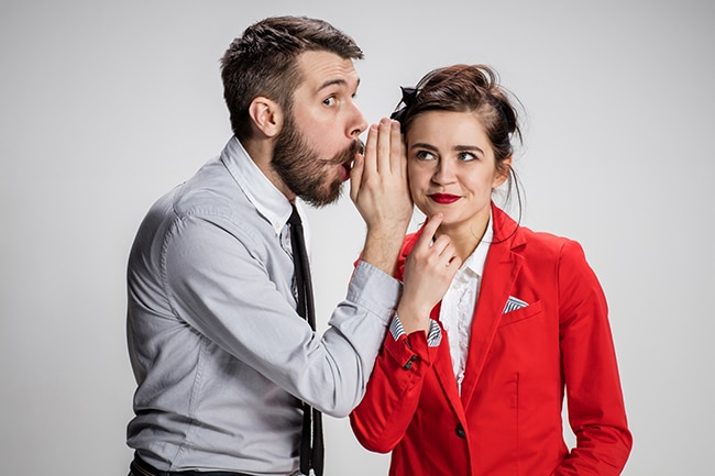 Young man telling gossips to his woman colleague at the office.
