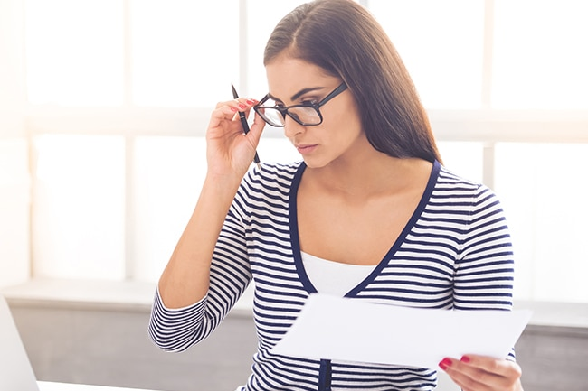 business lady in smart casual wear and eyeglasses is examining documents and using a laptop while working in office