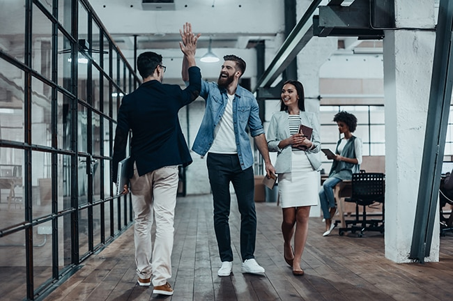 Full length of two cheerful young business people giving high-five while their colleague looking at them and smiling