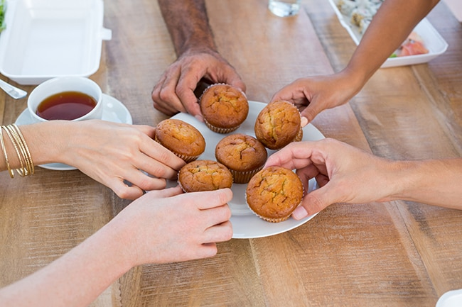 People taking a muffin from a white plate