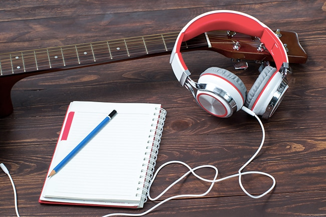 Notepad, guitar and headphone on a wooden floor