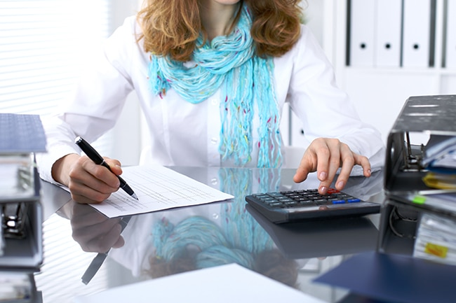Female bookkeeper working on a report using calculator