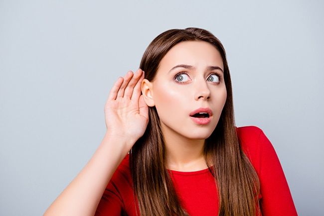 Girl with brown hair listening to someones conversation