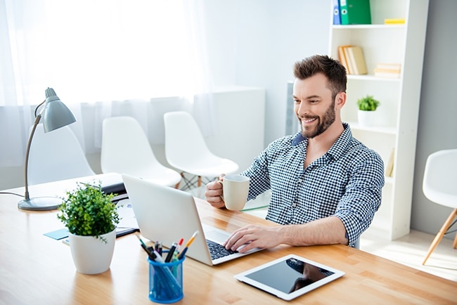 Young happy businessman drinking coffee while working on laptop