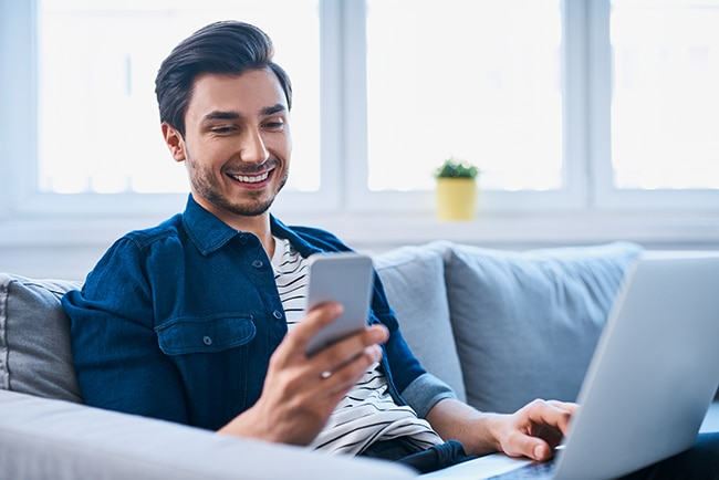 Young man sitting relaxed on sofa with laptop and smartphone
