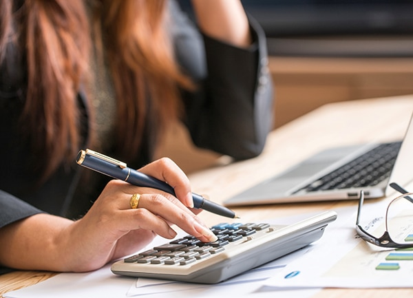 Close up of female accountant making calculations.