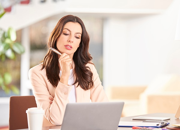 young businesswoman working on laptop while sitting at office.