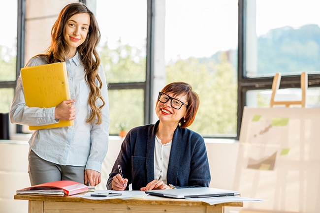 Portrait of a young and older businesswomen working together