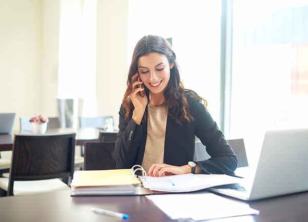 Shot of a young businesswoman sitting at office desk in front of laptop and making call