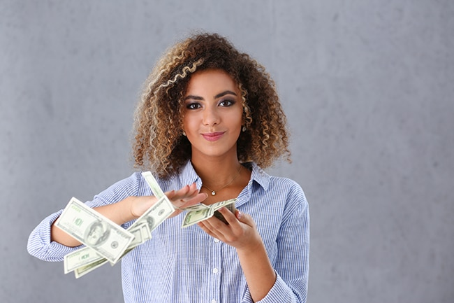 Young women throwing dollar bills