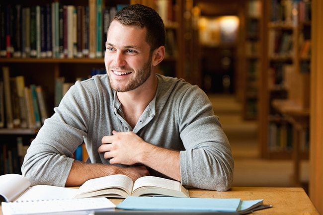 Smiling male student working in a library