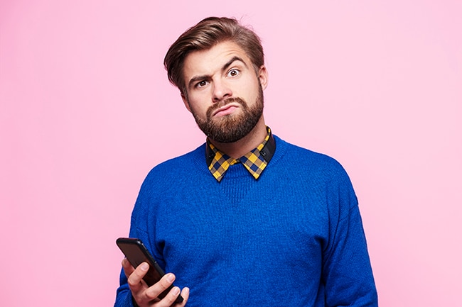 Man looking puzzled holding a mobile phone