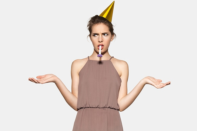 Young woman with festive hat and whistle at party fills disappointment