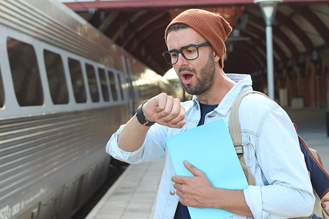 Shocked male after checking the time at the train station.