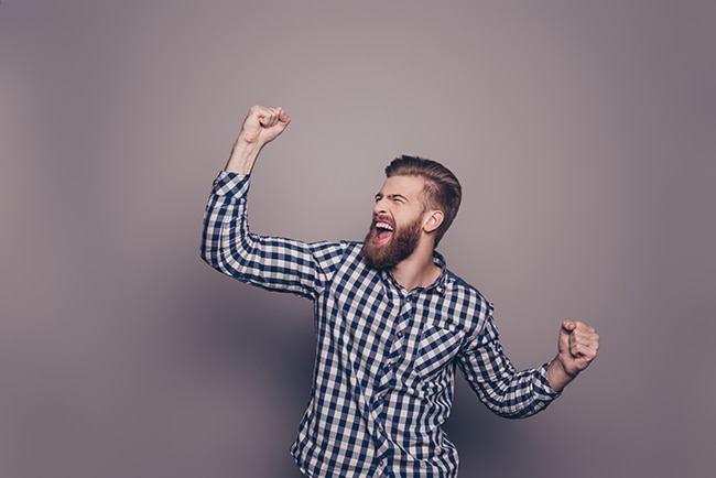 Stylish happy bearded man raised hands and shouting