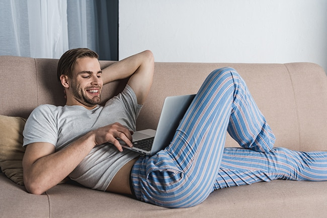 young relaxed freelancer in pajamas working with laptop on couch