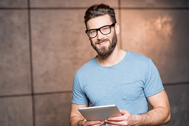 Portrait of a handsome man with digital tablet indoors