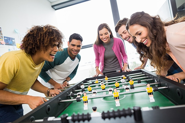 Happy executives playing table football in office