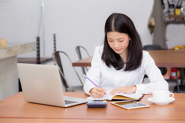 Business woman writing on notebook on table with laptop