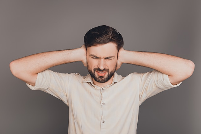 Man with headache covering ears from noise