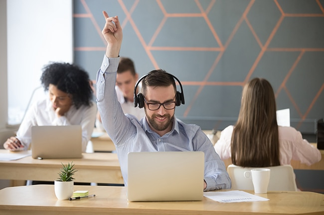 Excited male employee wearing headset dancing at workplace