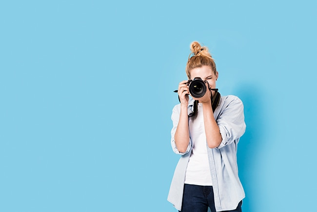 Young photographer standing against blue wall