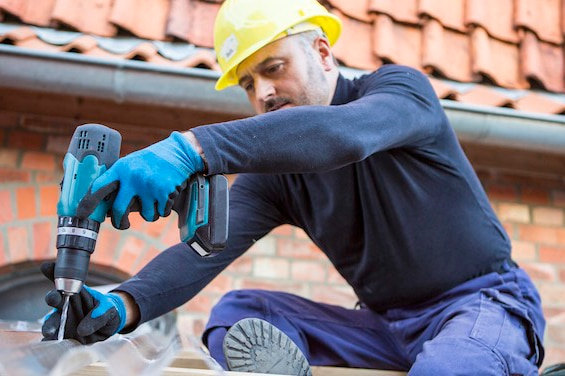 worker drills on a roof of a carport next to a house