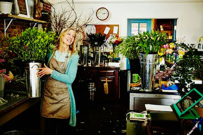 Smiling florist carrying bucket filled with flowers in workspace of floral shop