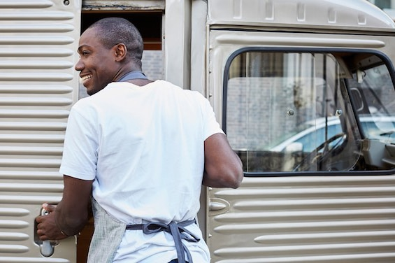 Smiling mid adult male owner opening door of food truck in city