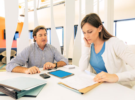 Male accountant reviewing paperwork with millennial client in office