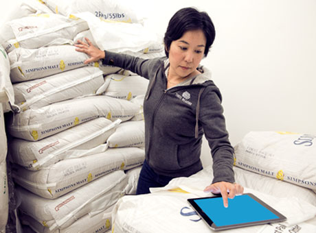 Female employee evaluating SEO on tablet near piles of malt in brewery